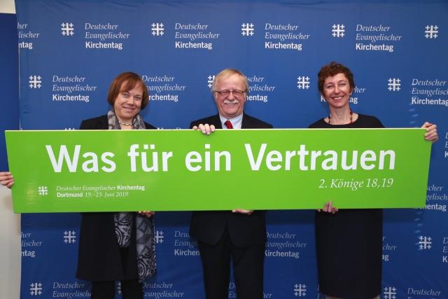 drei Personen präsentieren das Motto für den Kirchentag 2019