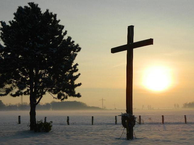 großes Holzkreuz im Schnee