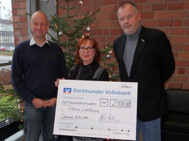 zwei Männer und eine Frau bei der symbolischen Scheckübergabe an die Aktion Lichtblicke