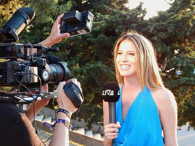 Moderatorin mit Mikrofon vor einer Kamera