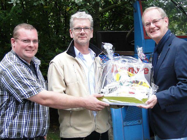 drei Männer bei einer symbolischen Spendenübergabe